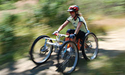 Adaptive Off-road cycling.  Picture of woman enjoying off-road cycling in adaptive bicycle.