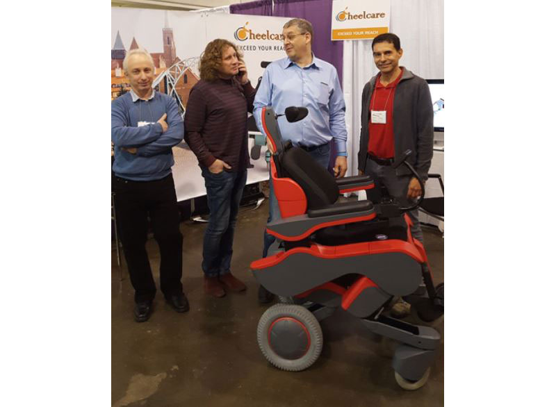 The CheelCare executive team, including co-founders Eugene Cherny –CEO, and Dima Paltsev –CFO. They stand in front of a Cheelcare banner and behind a red CheelCare Xceed power chair. Photo taken at the 2017 Abilities Expo in Toronto.