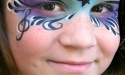 Face Painting: Image of smiling girl with blue and purple face paint.