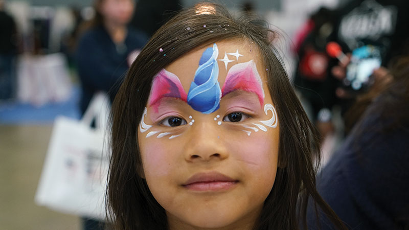 Child at Abilities Expo with face painted unicorn
