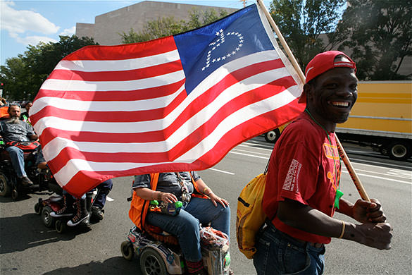 Civil rights for everyone.  Man carries US flag with wheelchair users behind him.