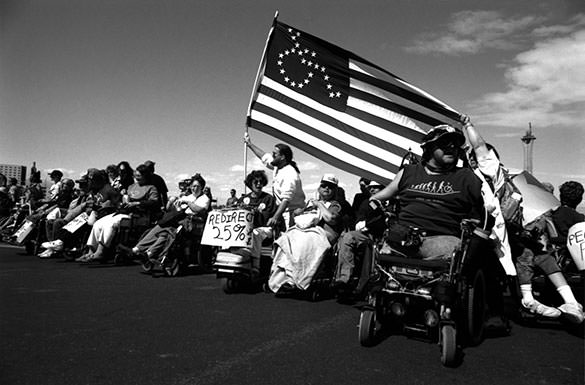 Wheelchair users with flag.