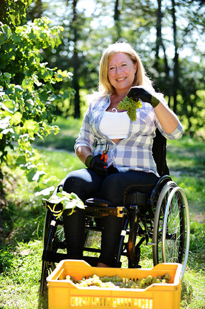 Smiling woman gardening form wheelchair.