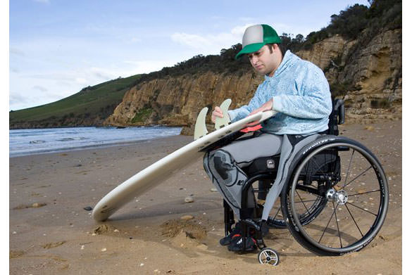 Sunrise Wheelchair image.  Man with surfboard at beach in a Sunset.
