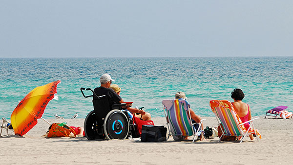 A group of people are sitting in beach chairs facing the ocean on a sunny day. One of the group is sitting in a wheelchair.